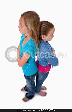 Portrait of girls standing back to back stock photo, Portrait of girls standing back to back against a white background by Wavebreak Media