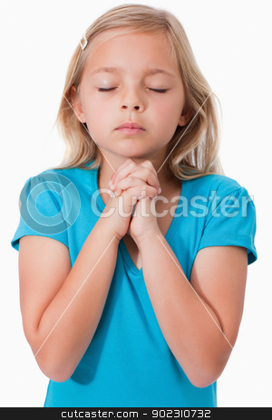 Portrait of a young girl praying stock photo, Portrait of a young girl praying against a white background by Wavebreak Media