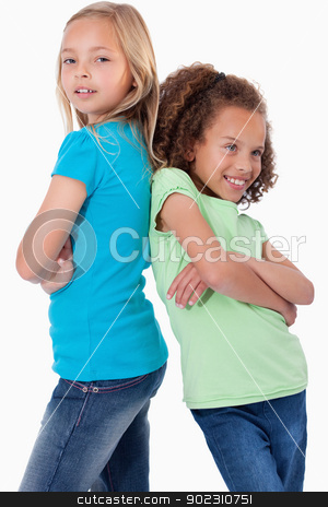 Portrait of smiling girls standing back to back stock photo, Portrait of smiling girls standing back to back against a white background by Wavebreak Media