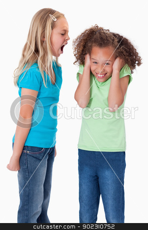 Portrait of an angry girl screaming at her friend stock photo, Portrait of an angry girl screaming at her friend against a white background by Wavebreak Media