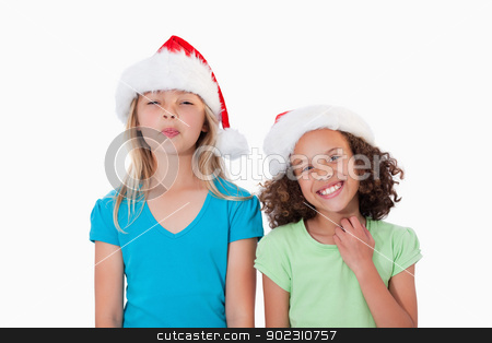 Cheerful girls with Christmas hats stock photo, Cheerful girls with Christmas hats against a white background by Wavebreak Media