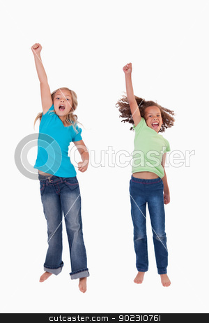 Portrait of girls jumping with their fists up stock photo, Portrait of girls jumping with their fists up against a white background by Wavebreak Media