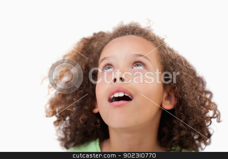 Close up of a girl looking above her stock photo, Close up of a girl looking above her against a white background by Wavebreak Media