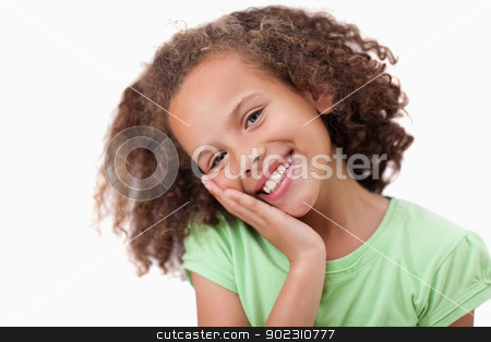 Cute girl with her hand on her cheek stock photo, Cute girl with her hand on her cheek against a white background by Wavebreak Media