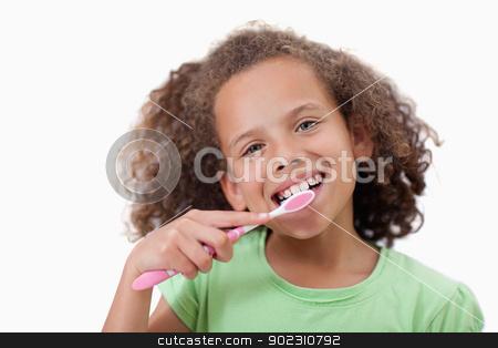 Cute girl brushing her teeth stock photo, Cute girl brushing her teeth against a white background by Wavebreak Media