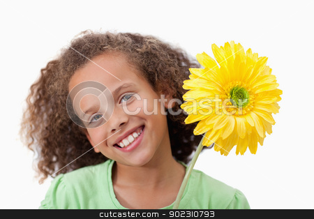 Cute girl holding a flower stock photo, Cute girl holding a flower against a white background by Wavebreak Media