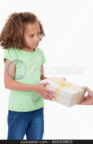 Portrait of a young girl receiving a gift stock photo, Portrait of a young girl receiving a gift against a white background by Wavebreak Media