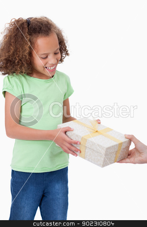 Portrait of a young girl receiving a present stock photo, Portrait of a young girl receiving a present against a white background by Wavebreak Media
