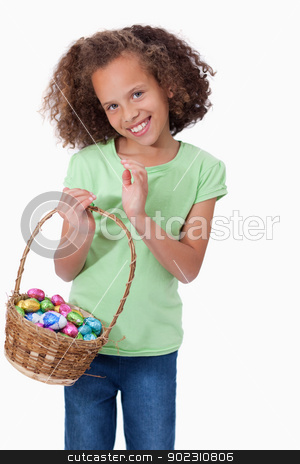 Portrait of a cute girl holding a basket full of Easter eggs stock photo, Portrait of a cute girl holding a basket full of Easter eggs against a white background by Wavebreak Media