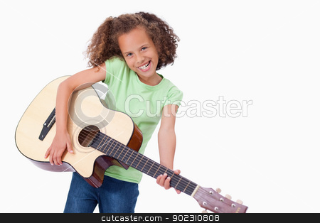 Happy girl playing the guitar stock photo, Happy girl playing the guitar against a white background by Wavebreak Media