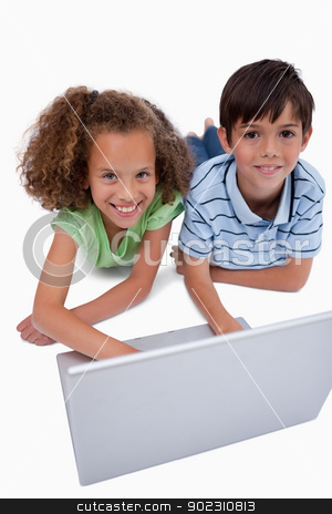 Portrait of children using a notebook while lying on the floor stock photo, Portrait of children using a notebook while lying on the floor against a white background by Wavebreak Media