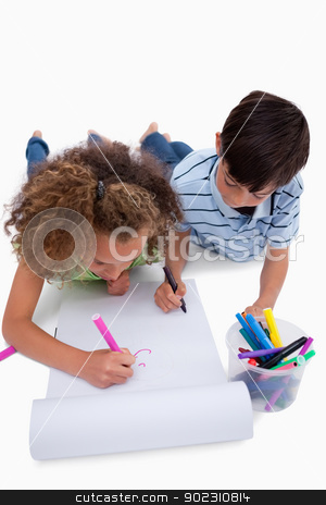 Portrait of children drawing while lying on the floor stock photo, Portrait of children drawing while lying on the floor against a white background by Wavebreak Media