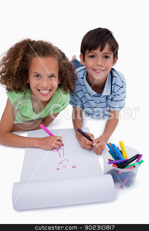 Portrait of smiling friends drawing while lying on the floor stock photo, Portrait of smiling friends drawing while lying on the floor against a white background by Wavebreak Media