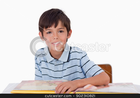 Cute boy reading a book stock photo, Cute boy reading a book against a white background by Wavebreak Media