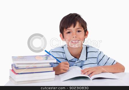 Boy doing his homework stock photo, Boy doing his homework against a white background by Wavebreak Media
