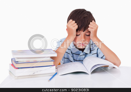 Focused boy learning his lessons stock photo, Focused boy learning his lessons against a white background by Wavebreak Media