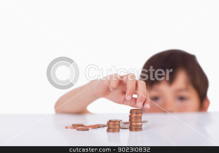 Boy counting his change stock photo, Boy counting his change against a white background by Wavebreak Media