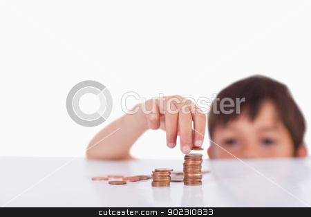 Young boy counting his change stock photo, Young boy counting his change against a white background by Wavebreak Media