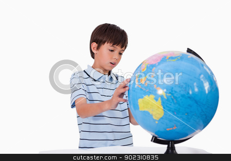 Boy looking at a globe stock photo, Boy looking at a globe against a white background by Wavebreak Media