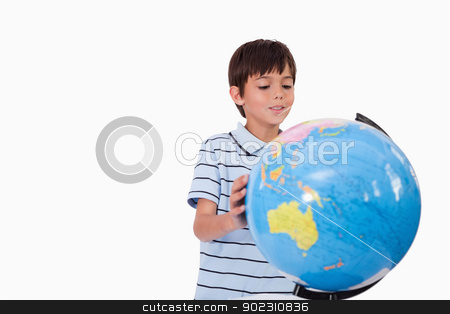 Smiling boy looking at a globe stock photo, Smiling boy looking at a globe against a white background by Wavebreak Media
