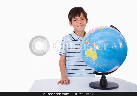 Smiling boy posing with a globe stock photo, Smiling boy posing with a globe against a white background by Wavebreak Media