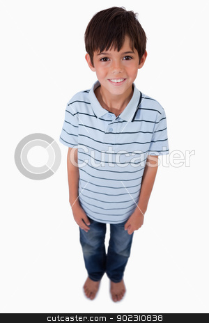 Portrait of a boy smiling at the camera stock photo, Portrait of a boy smiling at the camera against a white background by Wavebreak Media