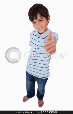 Portrait of a boy smiling at the camera with the thumb up stock photo, Portrait of a boy smiling at the camera with the thumb up against a white background by Wavebreak Media