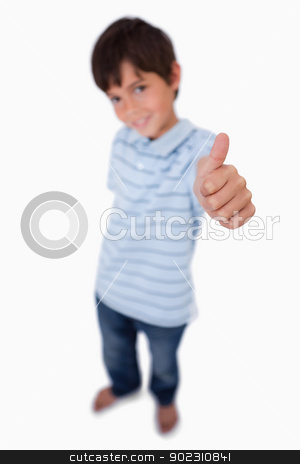 Portrait of a happy boy smiling at the camera with the thumb up stock photo, Portrait of a happy boy smiling at the camera with the thumb up against a white background by Wavebreak Media