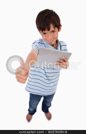 Portrait of a boy using a tablet computer with the thumb up stock photo, Portrait of a boy using a tablet computer with the thumb up against a white background by Wavebreak Media