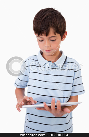 Portrait of a cute boy using a tablet computer stock photo, Portrait of a cute boy using a tablet computer against a white background by Wavebreak Media