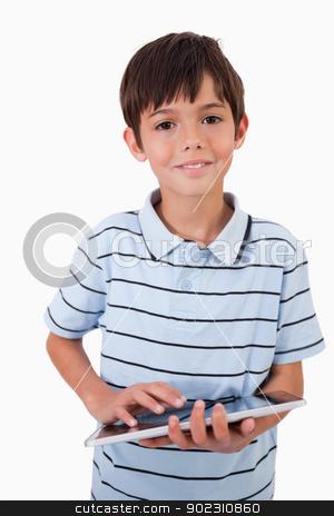Portrait of a cute little boy using a tablet computer stock photo, Portrait of a cute little boy using a tablet computer against a white background by Wavebreak Media