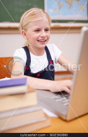 Portrait of a girl using a laptop stock photo, Portrait of a girl using a laptop in a classroom by Wavebreak Media