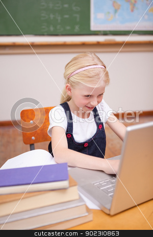 Portrait of a little girl using a laptop stock photo, Portrait of a little girl using a laptop in a classroom by Wavebreak Media