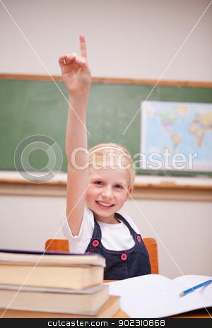 Portrait of a girl raising her hand stock photo, Portrait of a girl raising her hand in a classroom by Wavebreak Media