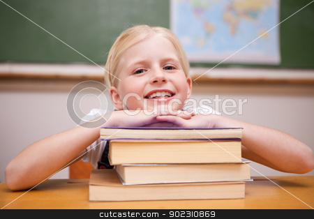 Girl leaning on books stock photo, Girl leaning on books in a classroom by Wavebreak Media