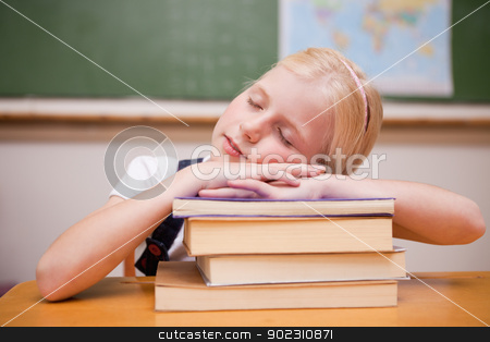 Girl sleeping on her books stock photo, Girl sleeping on her books in a classroom by Wavebreak Media