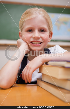 Portrait of a girl leaning on books stock photo, Portrait of a girl leaning on books in a classroom by Wavebreak Media