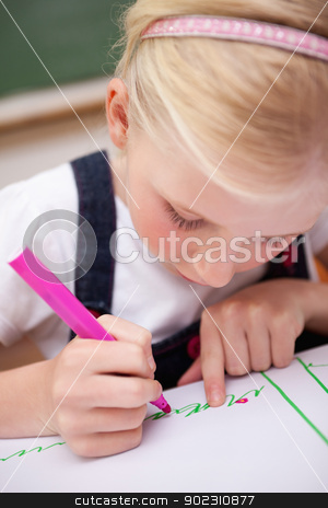 Portrait of a focused girl drawing stock photo, Portrait of a focused girl drawing in a classroom by Wavebreak Media