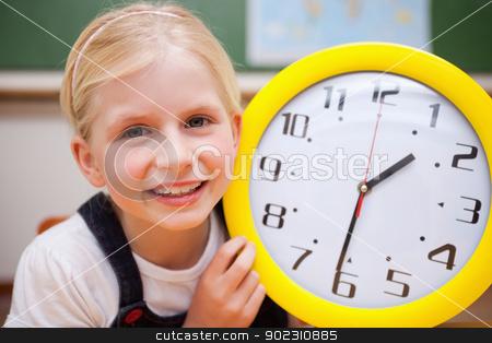 Schoolgirl showing a clock stock photo, Schoolgirl showing a clock in a classroom by Wavebreak Media