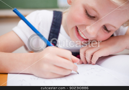 Close up of a schoolgirl writing something stock photo, Close up of a schoolgirl writing something in a classroom by Wavebreak Media