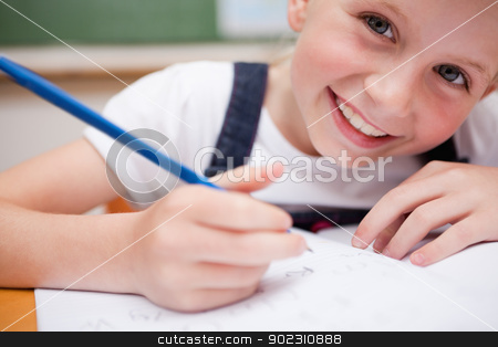 Close up of a smiling schoolgirl writing something stock photo, Close up of a smiling schoolgirl writing something in a classroom by Wavebreak Media