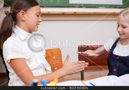 Schoolgirls playing together stock photo, Schoolgirls playing together in a classroom by Wavebreak Media