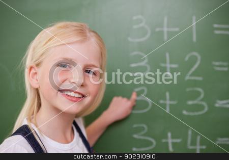 Blonde schoolgirl pointing at something stock photo, Blonde schoolgirl pointing at something on a blackboard by Wavebreak Media