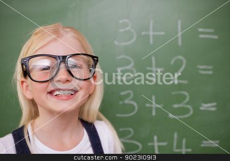 Smart schoolgirl posing in front of a blackboard stock photo, Smart schoolgirl posing in front of a blackboard in a classroom by Wavebreak Media