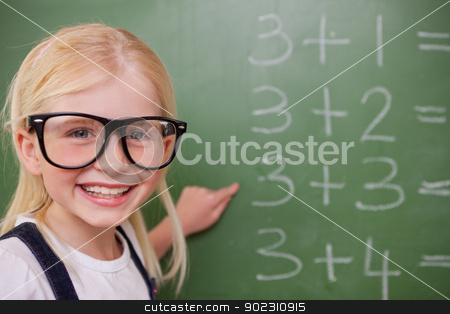 Smart schoolgirl pointing at something stock photo, Smart schoolgirl pointing at something on a blackboard by Wavebreak Media