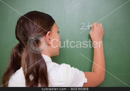 Schoolgirl writing an addition stock photo, Schoolgirl writing an addition on a blackboard by Wavebreak Media