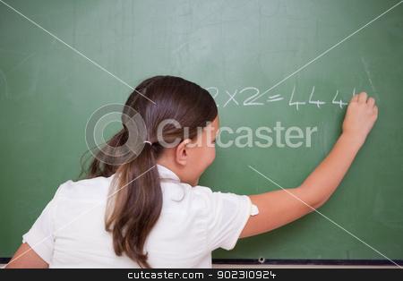 Schoolgirl writing numbers stock photo, Schoolgirl writing numbers on a blackboard by Wavebreak Media
