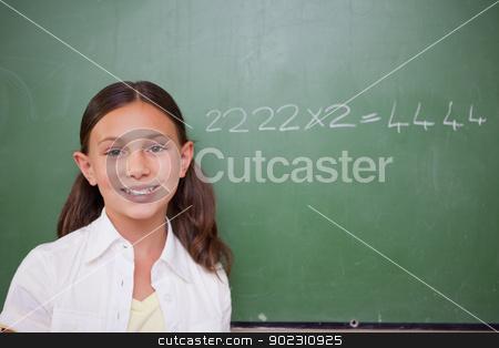 Schoolgirl posing in front of a chalkboard stock photo, Schoolgirl posing in front of a chalkboard in a classroom by Wavebreak Media