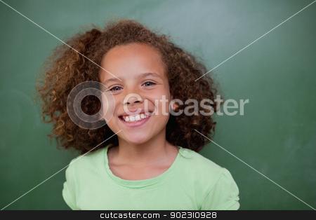 Schoolgirl posing in front of an empty chalkboard stock photo, Schoolgirl posing in front of an empty chalkboard in a classroom by Wavebreak Media