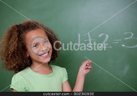 Cute schoolgirl pointing at an addition stock photo, Cute schoolgirl pointing at an addition on a blackboard by Wavebreak Media